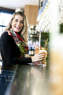 Portrait of happy woman with a cocktail at the counter of a bar - ERRF01134