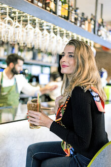 Smiling woman with a cocktail sitting at the counter of a bar - ERRF01137
