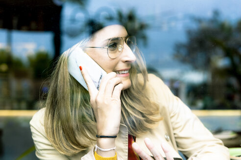 Woman behind windowpane on cell phone in a cafe - ERRF01138