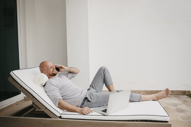 Happy man lying on lounge using cell phone and laptop - LHPF00527