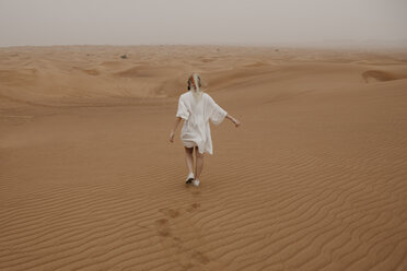 United Arab Emirates, Dubai, Lahbab Desert, woman walking in desert landscape - LHPF00530