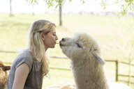 Woman feeding alpaca from mouth to mouth - FLLF00099