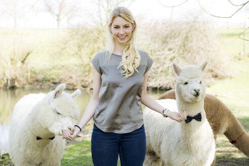 Portrait of happy woman feeding alpacas - FLLF00102