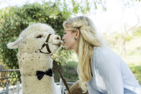 Woman feeding alpaca from mouth to mouth - FLLF00105