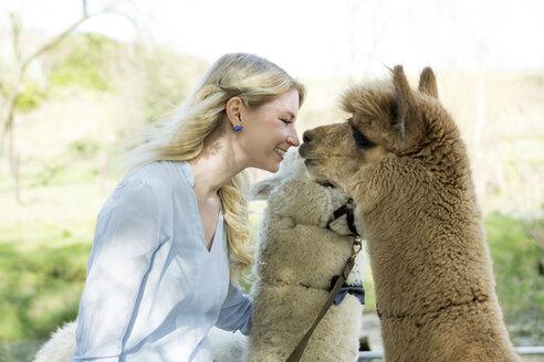 Happy woman cuddling her alpacas - FLLF00111