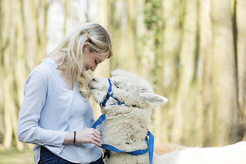 Happy woman cuddling white alpaca - FLLF00117