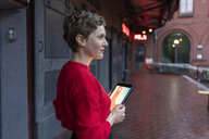 Germany, Berlin, profile of confident businesswoman with digital tablet outdoors - TAMF01276