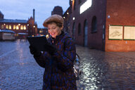 Germany, Berlin, portrait of smiling tourist using digital tablet at twilight - TAMF01285