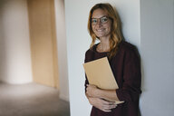 Smiling businesswoman leaning against a wall holding folder - GUSF01881