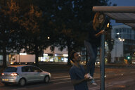 Young man giving girlfriend with cell phone a leg-up in the city at night - GUSF01896