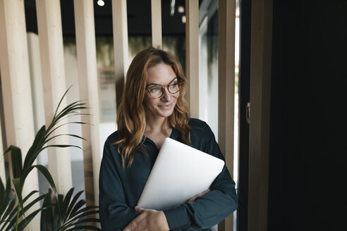 Smiling businesswoman holding laptop looking sideways - GUSF01914