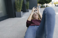 Happy young woman lying on bag using cell phone - GUSF01941