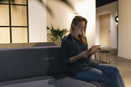 Businesswoman sitting on couch using tablet - GUSF01950