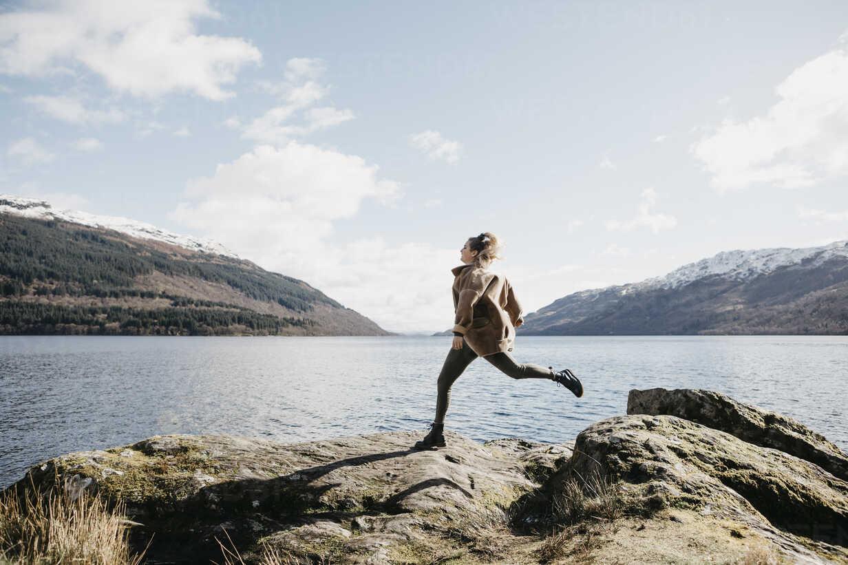 UK, Scotland, young woman running at Loch Lomond - LHPF00539 - letizia haessig photography/Westend61