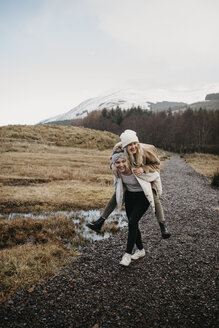 UK, Scotland, happy young woman carrying friend piggyback in rural landscape - LHPF00545