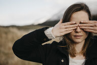 UK, Scotland, young woman covering her eyes in rural landscape - LHPF00554