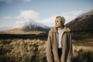 UK, Scotland, Loch Lomond and the Trossachs National Park, pensive young woman standing in rural landscape - LHPF00563