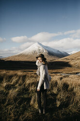 UK, Scotland, Loch Lomond and the Trossachs National Park, young woman wearing a hat in rural landscape - LHPF00566