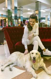 Smiling woman with dog sitting on couch in a vintage shop - MGOF03994