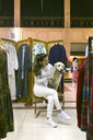 Smiling woman with dog sitting on chair in a vintage boutique - MGOF03997