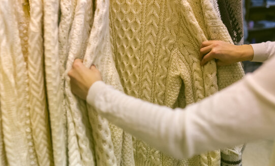 Close-up of woman shopping for a pullover in a vintage boutique - MGOF04000