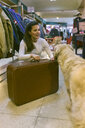 Woman with dog and old-fashioned suitcase in a vintage boutique - MGOF04003