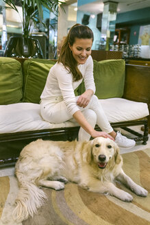Smiling woman with dog sitting on couch in a vintage shop - MGOF04024