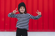 Portrait of winking little girl wearing striped shirt and black cap showing victory sign - ERRF01159
