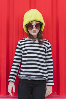 Portrait of astonished little girl wearing striped shirt, yellow cap and oversized sunglasses - ERRF01168