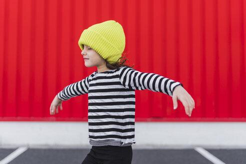 Little girl wearing striped shirt and yellow cap balancing - ERRF01171