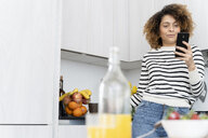 Woman standing in kitchen, using smartphone - FMOF00585