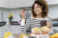 Woman sitting in kitchen, having breakfast - FMOF00588