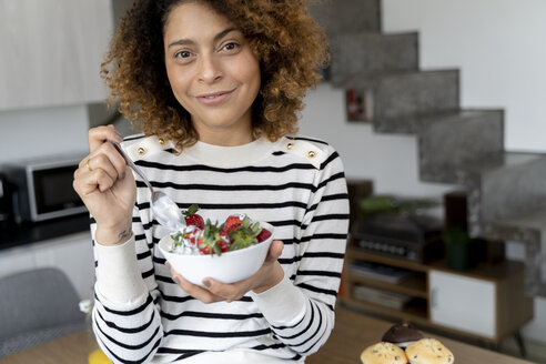 Woman eating strawberries at home - FMOF00591