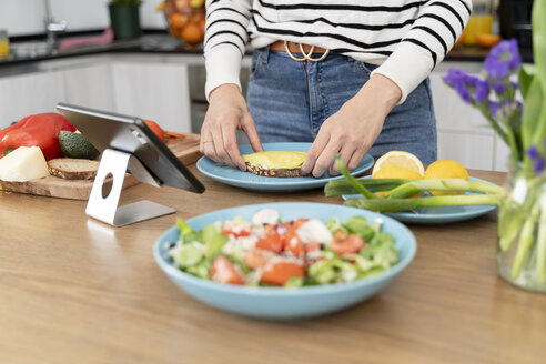 Woman standing in kitchen, preparing salad for lunch - FMOF00609