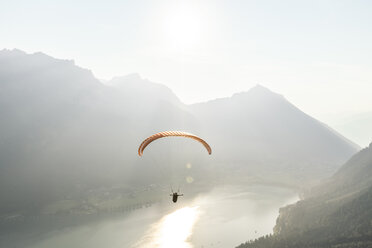 Austria, Tyrol, Paraglider over lake Achensee in the early morning - WFF00084