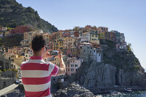 Italy, Liguria, La Spezia, Cinque Terre National Park, man using smartphone, photographing Manarola - EPF00594