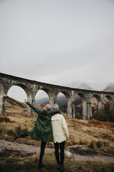 UK, Scotland, Highland, Glenfinnan Viaduct, rear view of female friends looking at view - LHPF00581