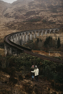 UK, Scotland, Highland, Glenfinnan Viaduct, rear view of female friends looking at view - LHPF00584