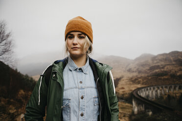 UK, Scotland, Highland, portrait of young woman at Glenfinnan Viaduct - LHPF00587