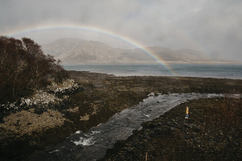 UK, Scotland, Highland, woman looking at rainbow above the sea - LHPF00614