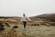 UK, Scotland, Isle of Skye, happy young woman running in rural landscape - LHPF00617