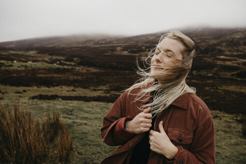 UK, Scotland, Highland, portrait of young woman with windswept hair in rural landscape - LHPF00620
