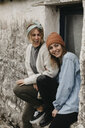 UK, Scotland, two laughing young women at a building - LHPF00632