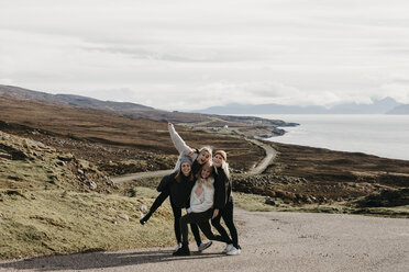 UK, Scotland, Highland, happy female friends on a road at the coast - LHPF00653