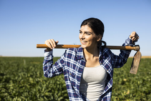 Young woman farmer with hoe on field - ABZF02323
