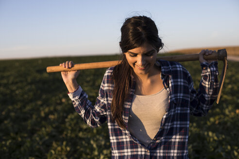 Young woman farmer with hoe on field - ABZF02341