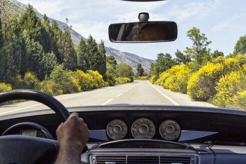 Mann am Steuer seines Autos, Blick auf Strasse mit blühendem Ginster, Tacho, Griechenland - MAMF00538
