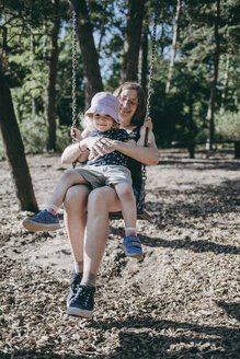 Happy mother with little daughter on swing on a playground - DWF00393