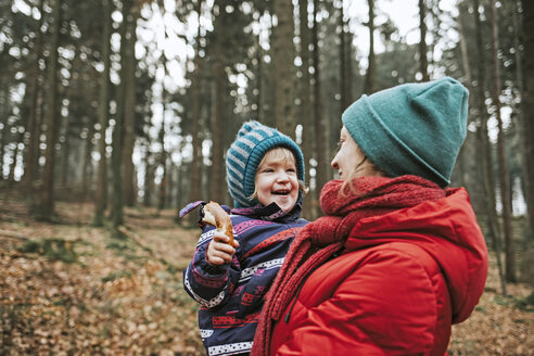 Mother carrying happy little daughter in autumnal forest - DWF00408