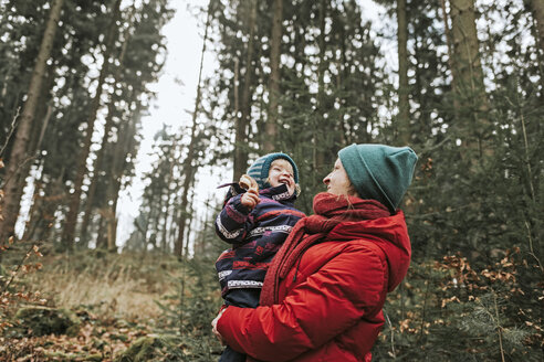 Mother carrying happy little daughter in autumnal forest - DWF00411